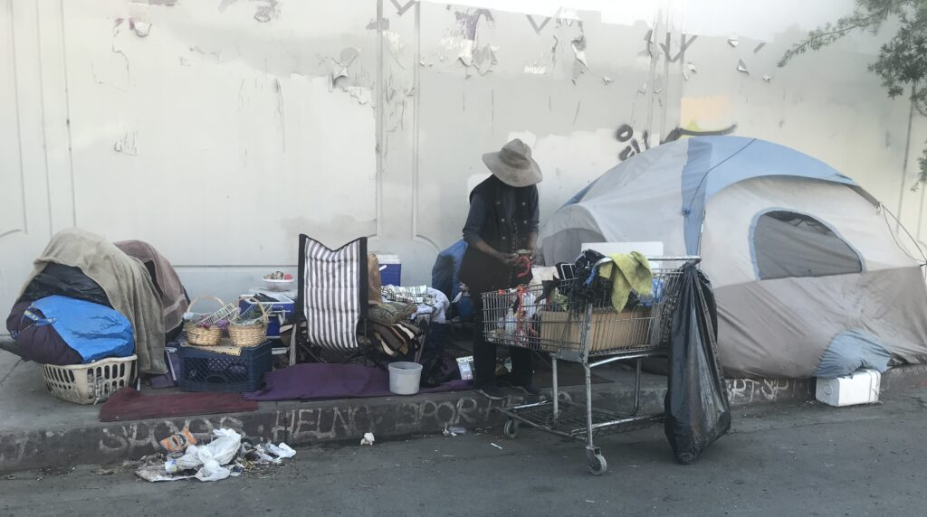 A photo of a homeless individual with a tent, cart and other belongings a few blocks from the Lotus shelter