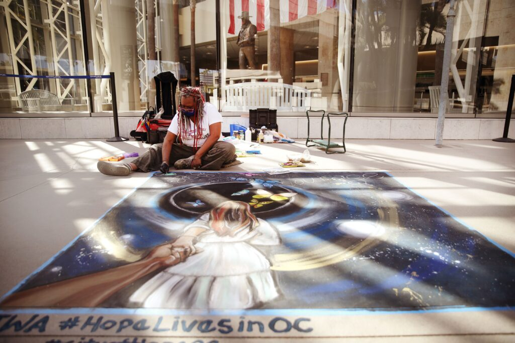 A photo of an artist working on a piece of 'Hope Lives in OC' artwork at John Wayne Airport